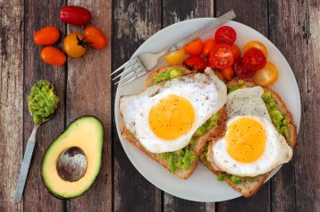 Healthy avocado, egg open sandwiches on a plate with cherry toma